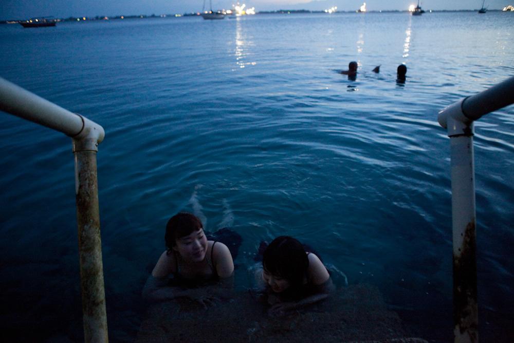 Japanese students, Mariko and Kana, Mick and Rico swimming in the lagoon at sunset / Photo: Jessie Boylan